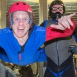 man flying in wind tunnel with instructor