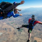 Two skydivers jump in the air.