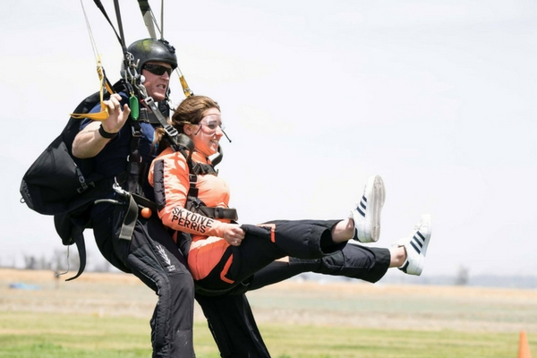 girl lands from first time skydiving experience