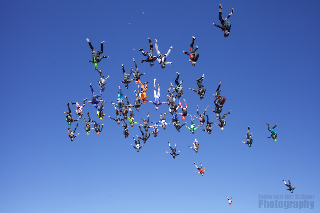 A group of skydivers in a vertical formation.
