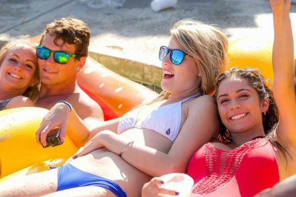 girls and guys lounge at Skydive Perris pool