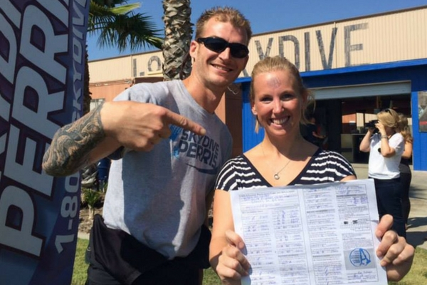 woman proudly holds skydiving license