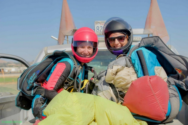 licensed skydivers ride in back of truck at dropzone