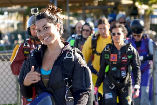 woman gives thumbs up on the way to skydiving plane