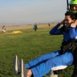 tandem student lifts legs for skydiving landing