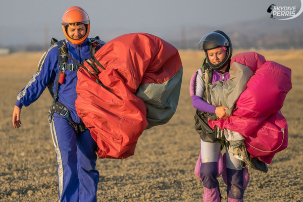 2 experienced skydivers walk back to hangar holding parachutes