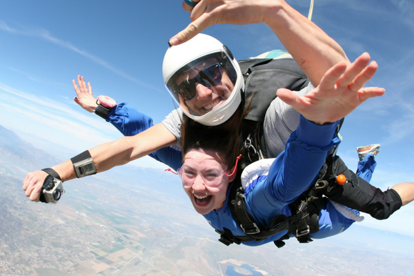 woman smiles with tandem skydiving instructor