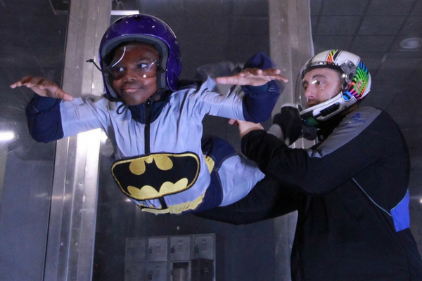 young child indoor skydiving in tunnel with instructor