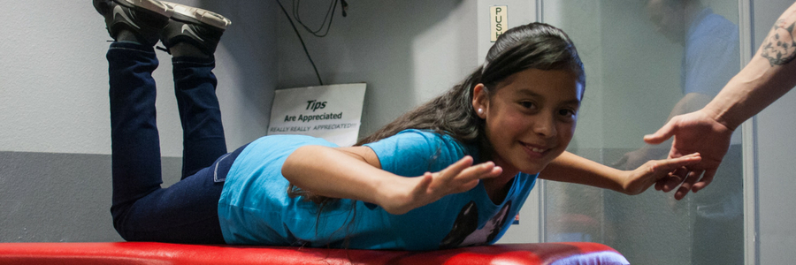 young girl practices body flight position with indoor skydiving instructor
