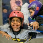 young boy smiles while indoor skydiving