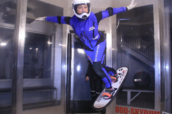 female instructor indoor skydiving on snowboard