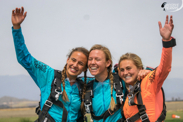 3 girls smile and embrace after landing from first tandem skydive