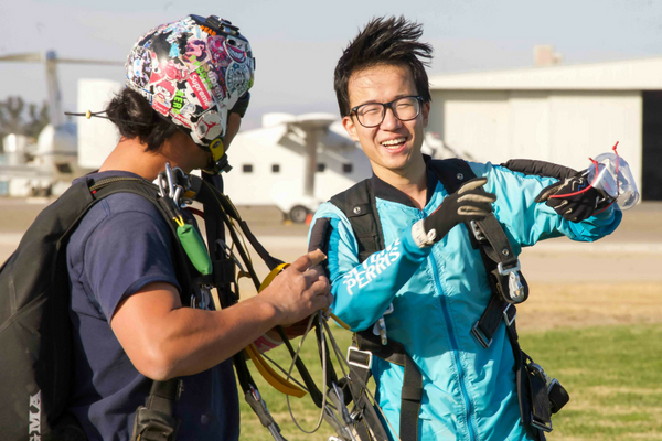 tandem skydiver talks with instructor before the jump