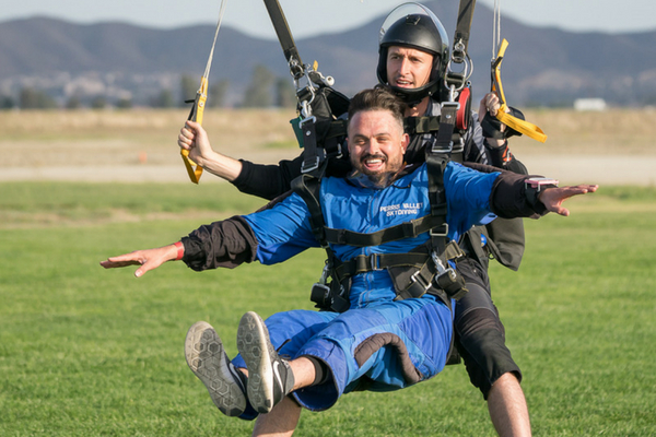 tandem skydiving student and instructor land from skydive