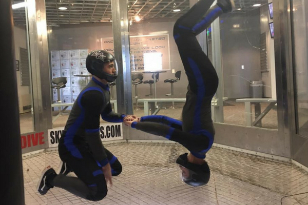 coach steadies indoor skydiver while they work on upside down position