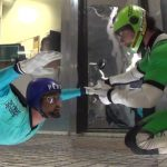 indoor skydiving coach works one on one with student in the wind tunnel