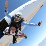 young man exits skydiving plan with instructor