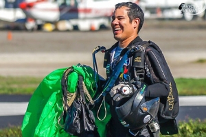 Anderson Briglia smiles holding canopy in landing area at Skydive Perris