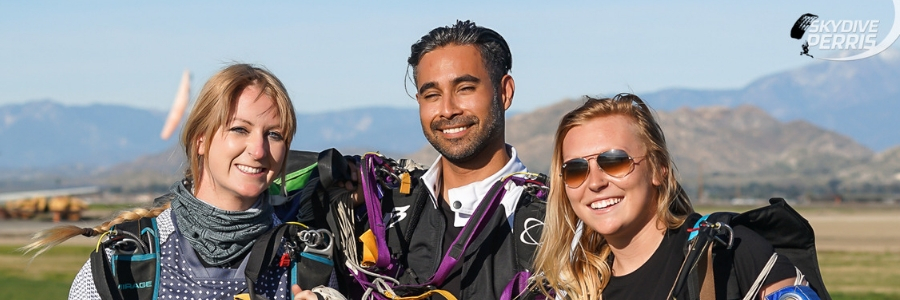 two young women and a young man smile for camera after skydiving at Perris