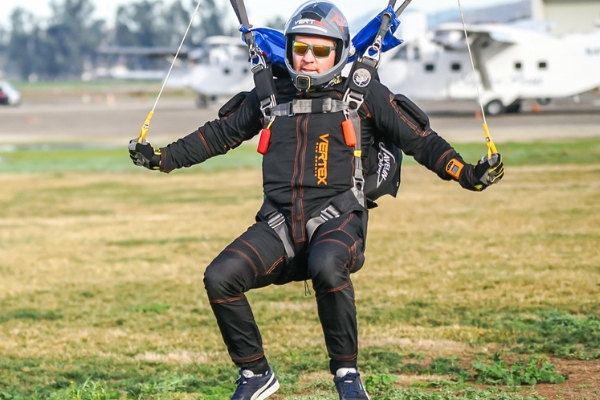 male skydiver with hands on toggles landing canopy with control