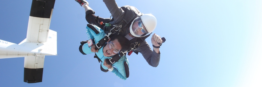 first time skydiving student opens mouth with excitement in skydiving freefall