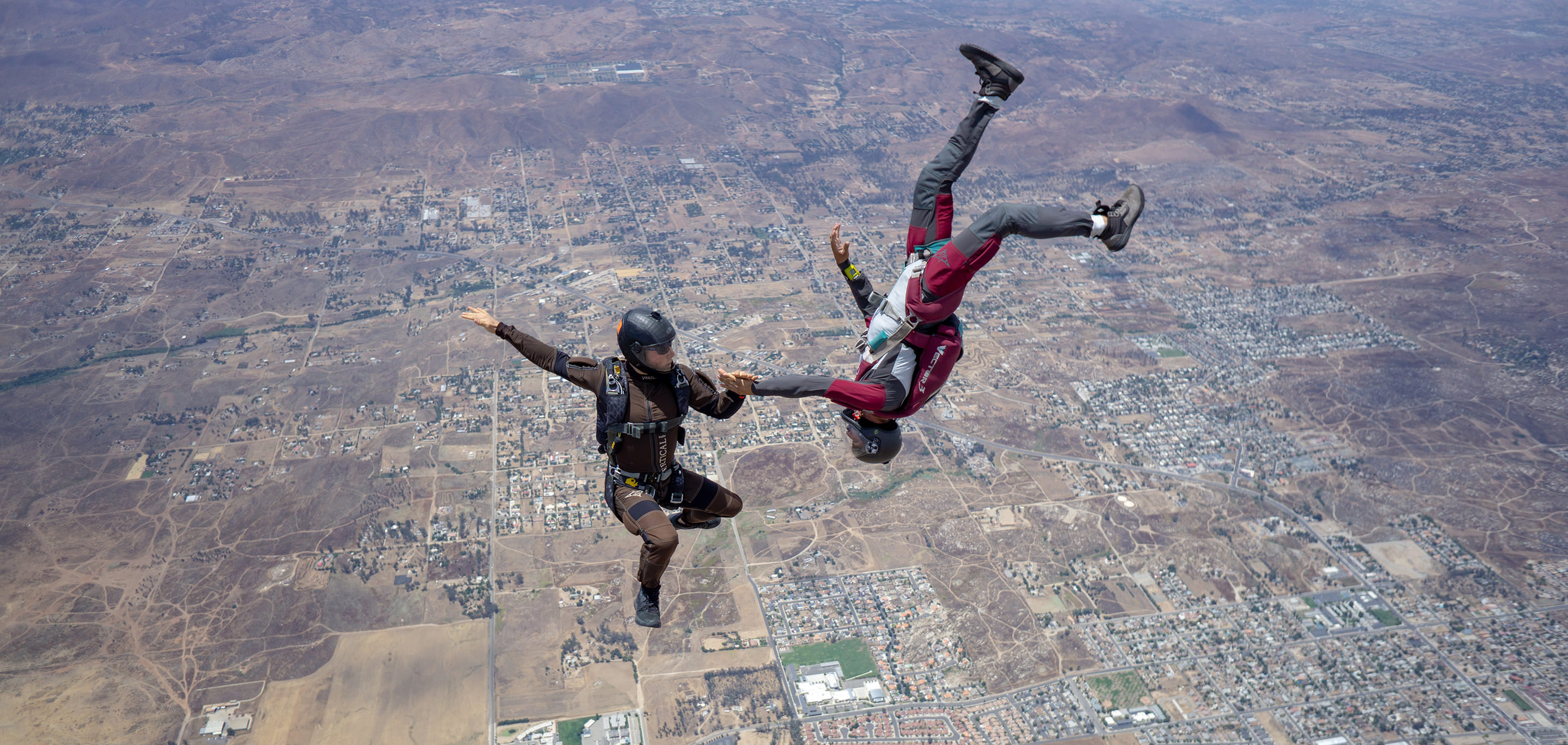 Two skydivers fly through the sky.